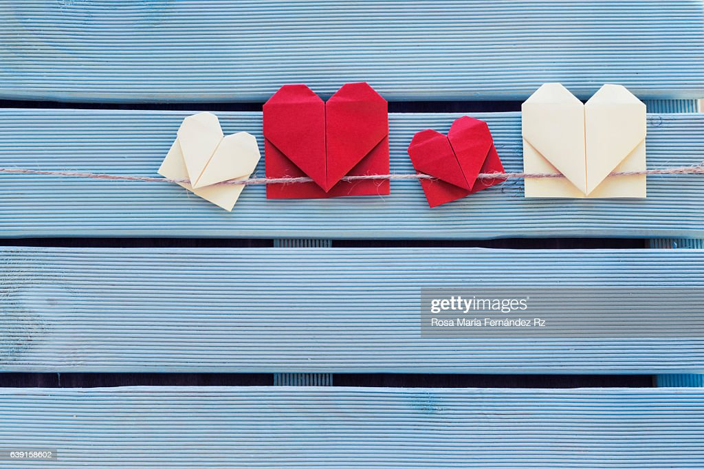 Origami heart bookmark hanging on blue wooden background. Subject captured againt soft window lighting on a blue wooden background. Overhead and copy space. : Stock Photo