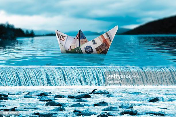 Origami paper boat of euro notes on waterfall