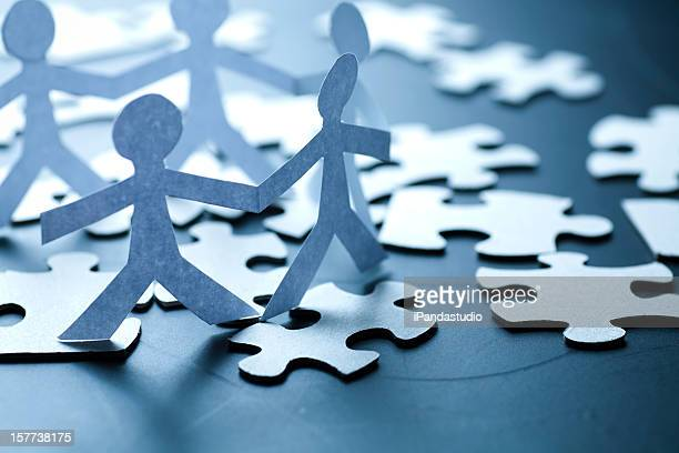 Origami paper people holding hands standing on jigsaw pieces