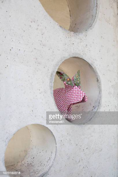 Origami rabbit sitting in hole