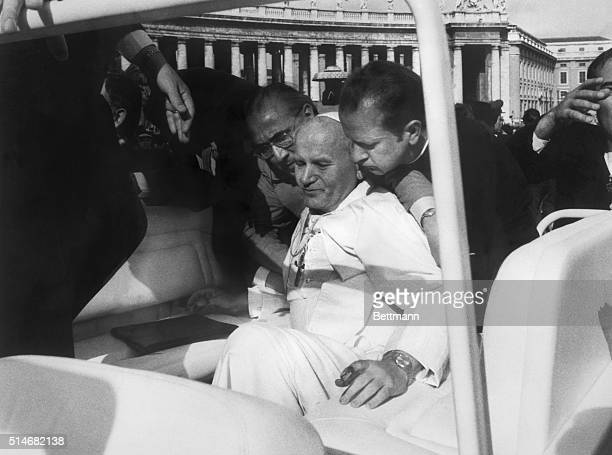 5/14/81Vatican City Blood on his hands Pope John Paul II is assisted by aides moments after he was shot while riding in his open car in St Peter's...