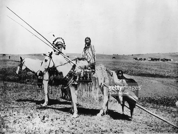 'A Blackfoot chief and squaw' The family is traveling on horseback carrying a child on a travois
