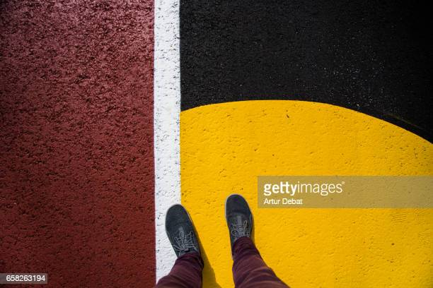 Original composition with vivid colors taken from personal perspective with feet and legs on the street.