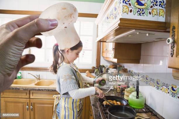 Original picture of girl cooking at home doing the mother role in kitchen with funny moment using mushroom like chef hat playing with perspective from photographer perspective.