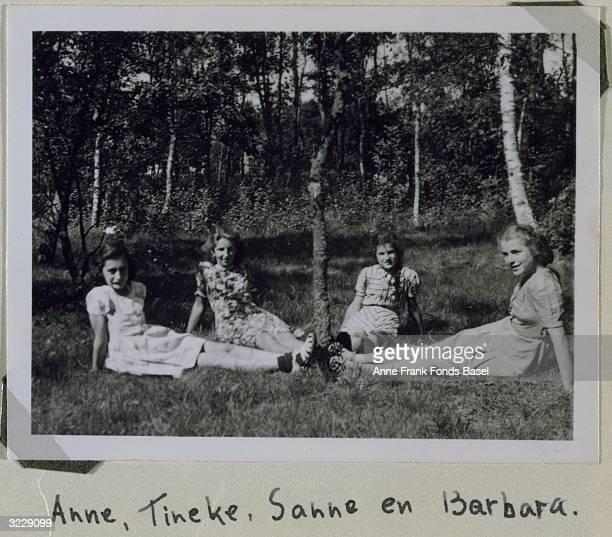From left to right Anne Frank Tineke WillegenGastonides Sanne and her sister Barbara Ledermann sit outdoors with their legs outstretched in the grass...