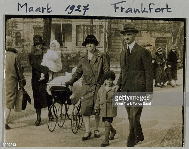 From left to right the mother of Anne Frank Edith Frank holds her nephew Bernd as she walks with Dadi who pulls Margot in a baby carriage Stephan...