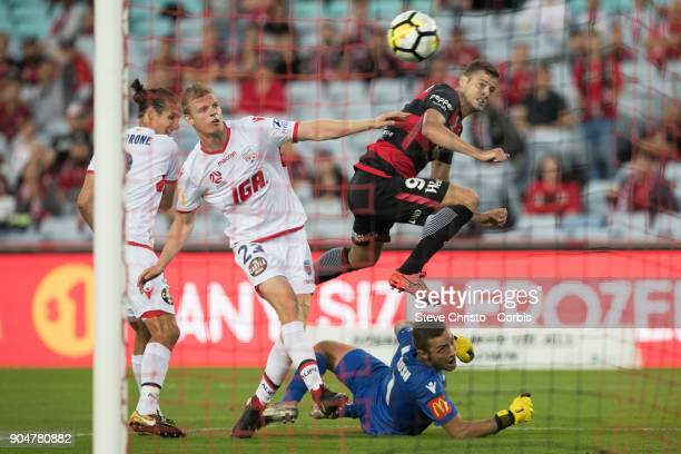 Oriol Riera of the Wanderers shoots for goal and leaps over United's goalkeeper Daniel Margush during the round fifteen of the ALeague match between...