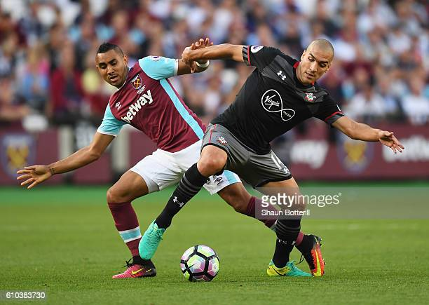 Oriol Romeu of Southampton holds off Dimitri Payet of West Ham United during the Premier League match between West Ham United and Southampton at...