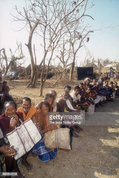 Orissa Cyclone Victims sitting in a Q waiting for Relief Material