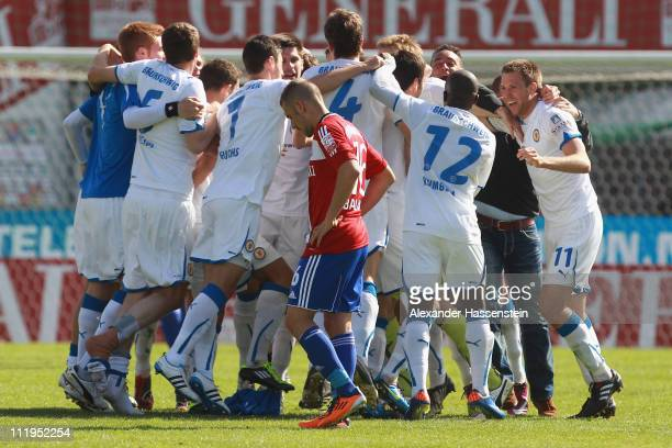 Orkan Balkan of Unterhaching looks dejected whilst players of Braunschweig celebrate after the Third League match between SpVgg Unterhaching and...