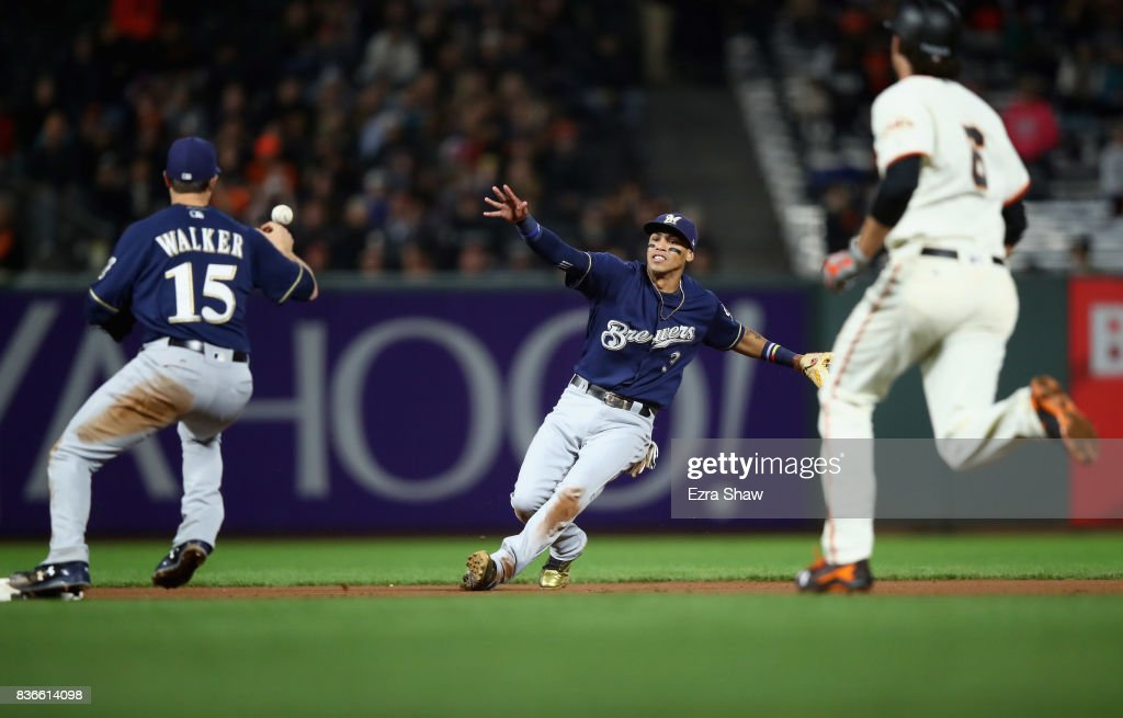 Orlando Arcia #3 flips the ball to Neil Walker #15 of the Milwaukee Brewers, who dropped the ball to allow Jarrett Parker #6 of the San Francisco Giants to be safe at second base in the fourth inning at AT&T Park on August 21, 2017 in San Francisco, California.