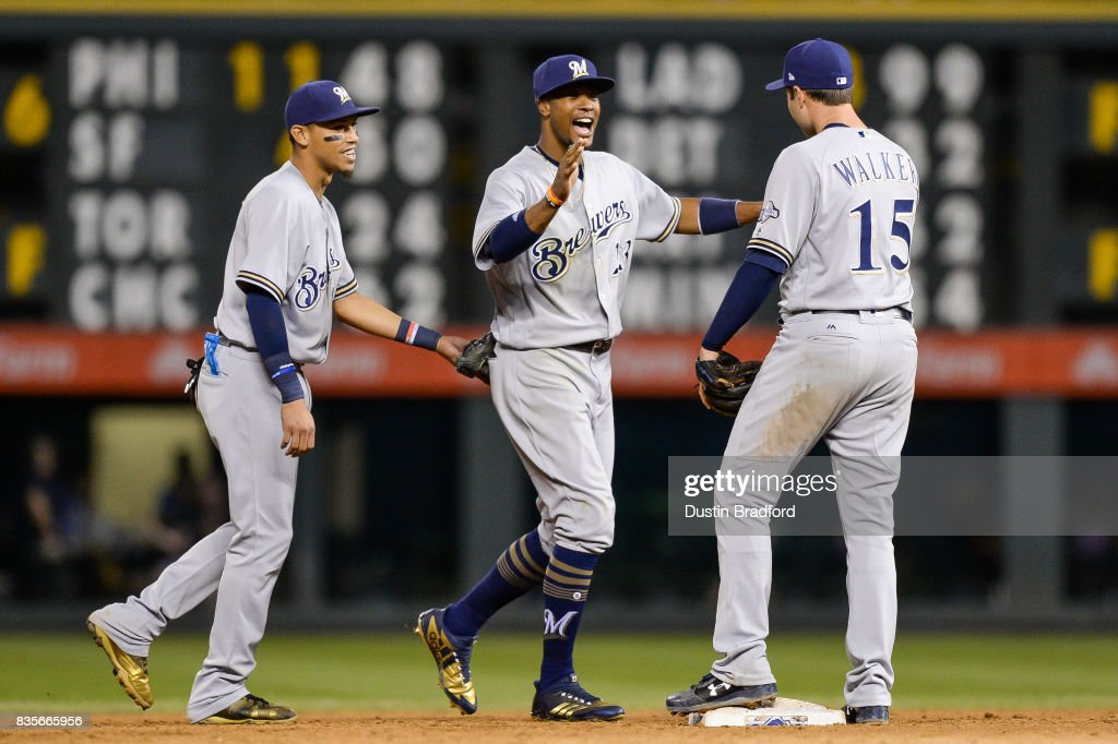 Orlando Arcia #3, Keon Broxton #23, and Neil Walker #15 of the Milwaukee Brewers celebrate a 6-3 win over the Colorado Rockies at Coors Field on August 19, 2017 in Denver, Colorado.