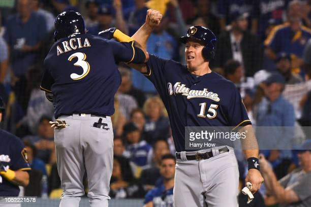 Orlando Arcia of the Milwaukee Brewers celebrates with Erik Kratz after hitting a 2run home run off Walker Buehler of the Los Angeles Dodgers in the...