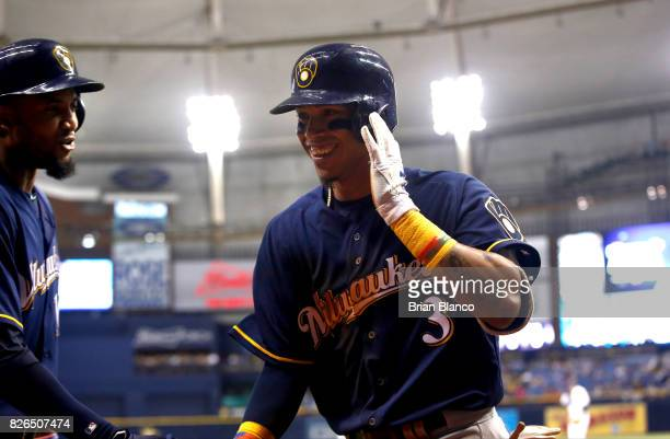 Orlando Arcia of the Milwaukee Brewers celebrates with teammate Domingo Santana as he makes his way back to the dugout after hitting a home run off...