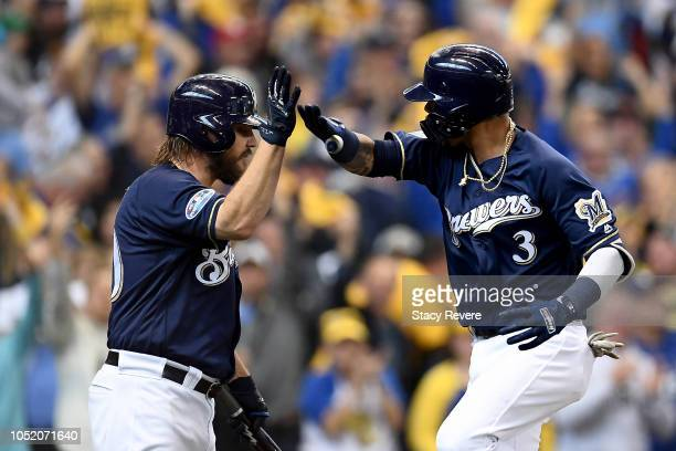 Orlando Arcia of the Milwaukee Brewers celebrates with teammate Wade Miley after hitting a solo home run against HyunJin Ryu of the Los Angeles...