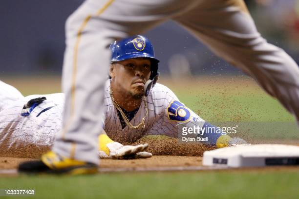 Orlando Arcia of the Milwaukee Brewers dives into third base past Jose Osuna of the Pittsburgh Pirates in the fifth inning at Miller Park on...