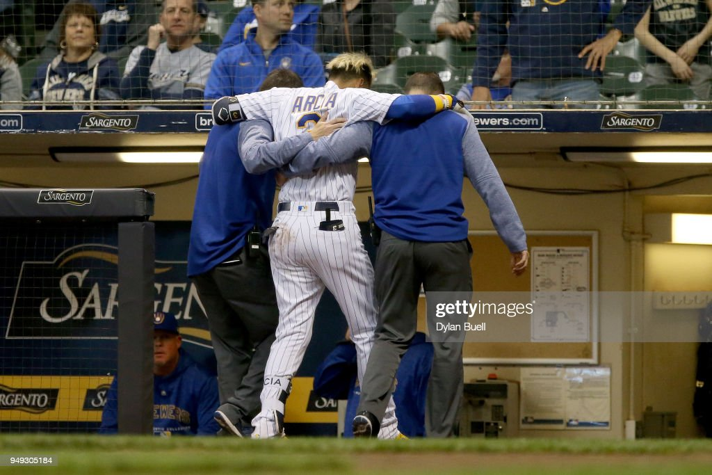 Orlando Arcia #3 of the Milwaukee Brewers is helped off the field after being injured in the eighth inning against the Miami Marlins at Miller Park on April 20, 2018 in Milwaukee, Wisconsin.