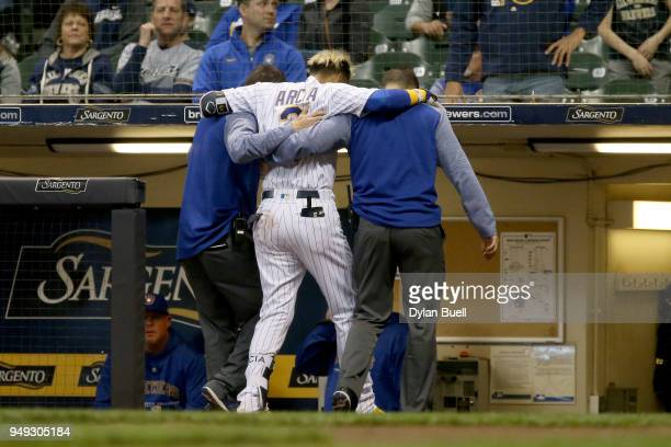 Orlando Arcia of the Milwaukee Brewers is helped off the field after being injured in the eighth inning against the Miami Marlins at Miller Park on...
