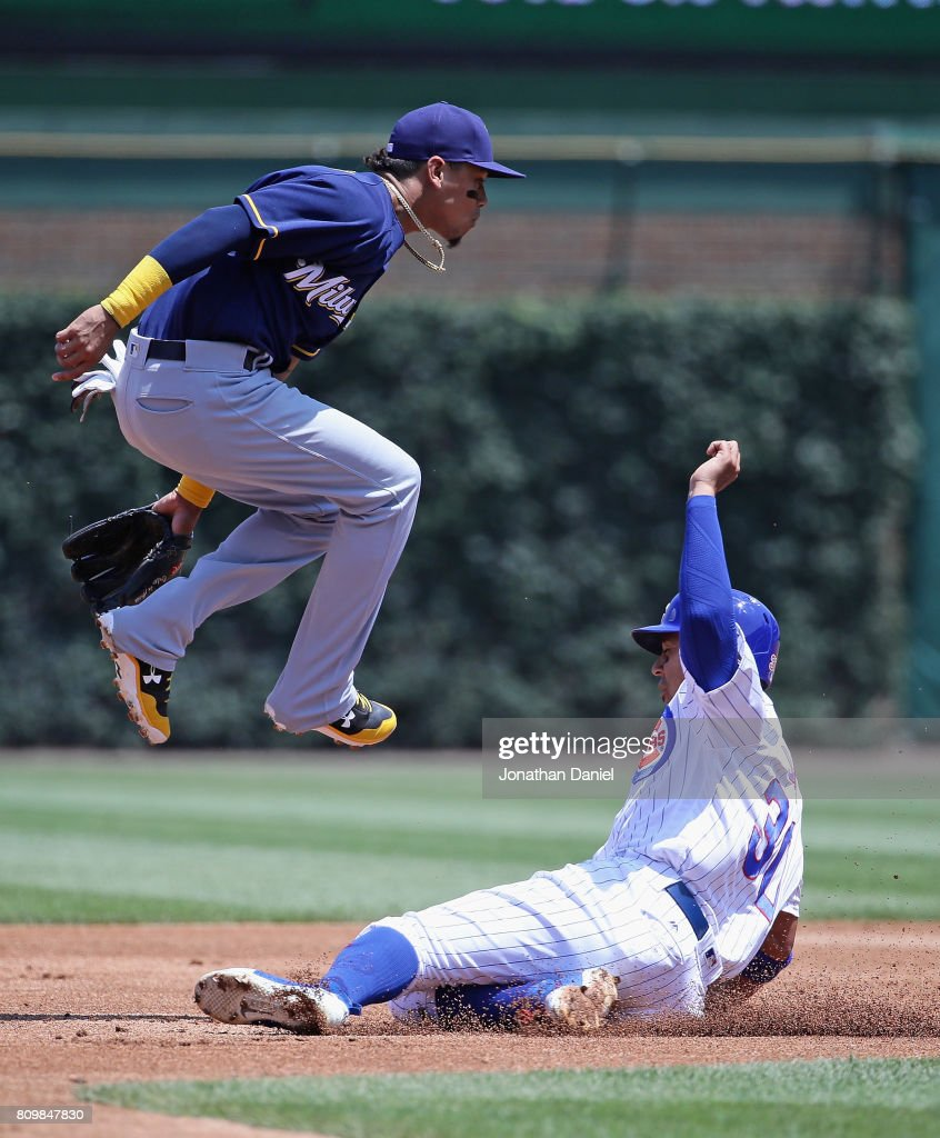 Orlando Arcia #3 of the Milwaukee Brewers leaps over Jon Jay #30 of the Chicago Cubs as he turns a double play in the 1st inning at Wrigley Field on July 6, 2017 in Chicago, Illinois.