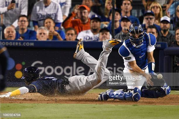 Orlando Arcia of the Milwaukee Brewers slides home safely to score a run against Austin Barnes of the Los Angeles Dodgers during the fifth inningin...