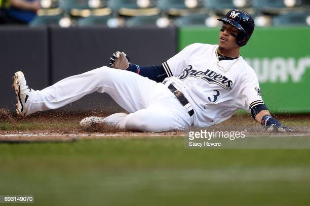 Orlando Arcia of the Milwaukee Brewers slides safely into home during the second inning against the San Francisco Giants at Miller Park on June 6...