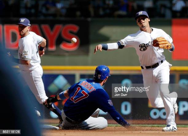 Orlando Arcia of the Milwaukee Brewers throws to first base after forcing out Kris Bryant of the Chicago Cubs for a double play to end the first...