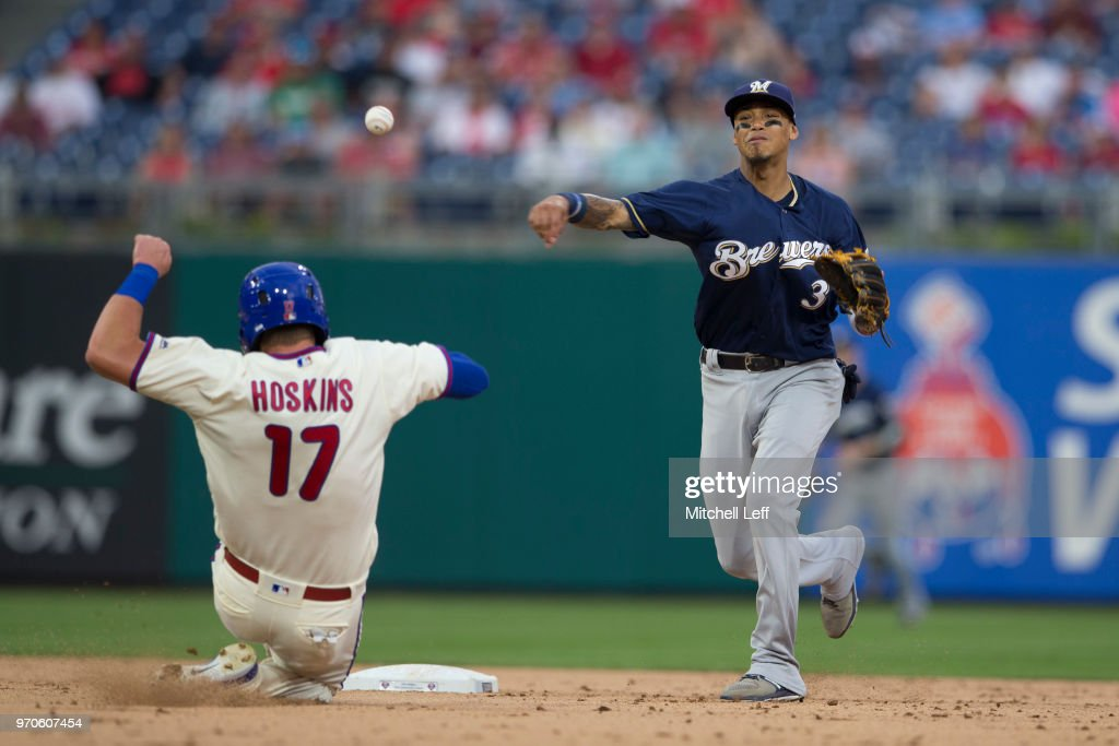 Orlando Arcia #3 of the Milwaukee Brewers turns a double play against Rhys Hoskins #17 of the Philadelphia Phillies in the bottom of the eighth inning at Citizens Bank Park on June 9, 2018 in Philadelphia, Pennsylvania. The Brewers defeated the Phillies 12-3.