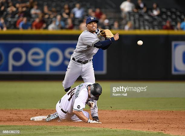 Orlando Arcia of the Milwaukee Brewers turns a double play over Paul Goldschmidt of the Arizona Diamondbacks during the eighth inning at Chase Field...