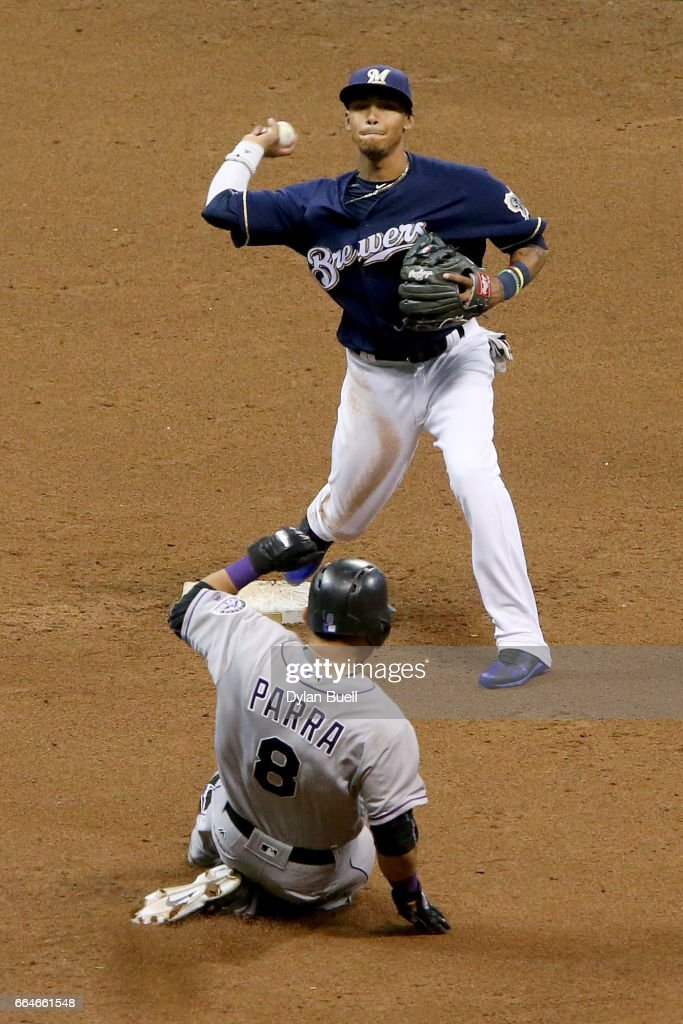 Orlando Arcia #3 of the Milwaukee Brewers turns a double play past Gerardo Parra #8 of the Colorado Rockies in the sixth inning at Miller Park on April 4, 2017 in Milwaukee, Wisconsin.