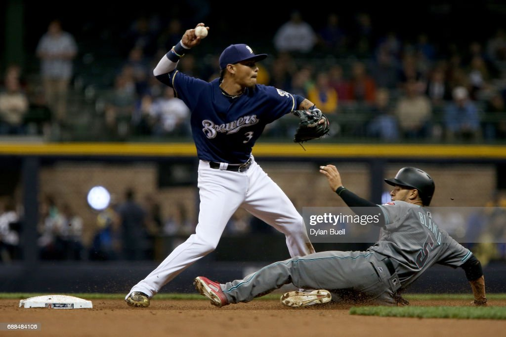 Orlando Arcia #3 of the Milwaukee Brewers turns a double play past Gregor Blanco #5 of the Arizona Diamondbacks in the fifth inning at Miller Park on May 25, 2017 in Milwaukee, Wisconsin.