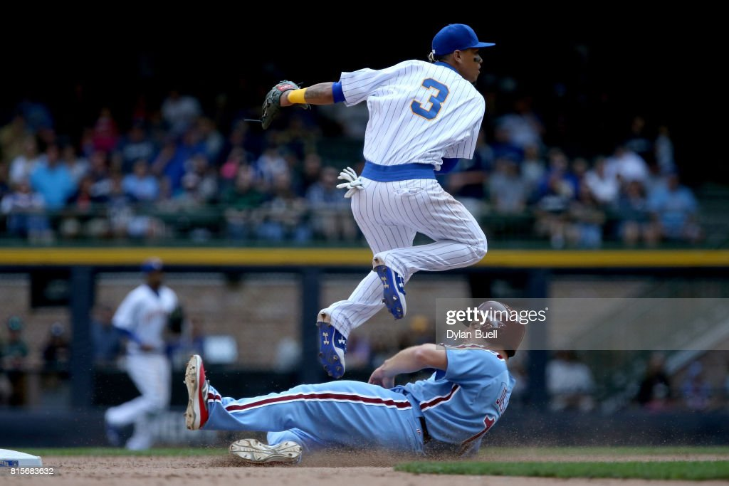 Orlando Arcia #3 of the Milwaukee Brewers turns a double play past Andrew Knapp #34 of the Philadelphia Phillies in the seventh inning at Miller Park on July 16, 2017 in Milwaukee, Wisconsin.