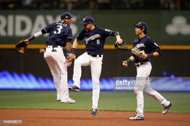 Orlando Arcia, Ryan Braun and Christian Yelich of the Milwaukee Brewers celebrate after the Brewers won Game 2 of the NLDS against the Colorado...