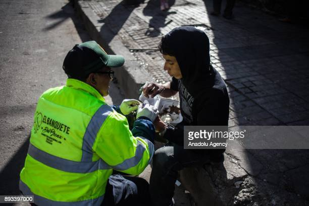Orlando Beltran helps a homeless man whose face has gotten infected by giving food in Bogota Colombia on December 15 2017 Homeless people eat their...