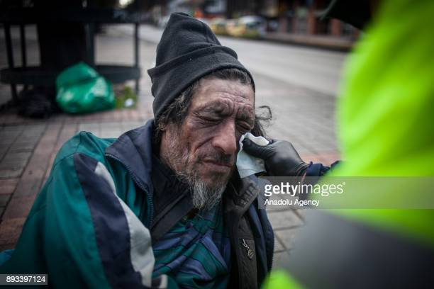Orlando Beltran helps a homeless man whose face has gotten infected in Bogota Colombia on December 15 2017 Homeless people eat their meal distributed...