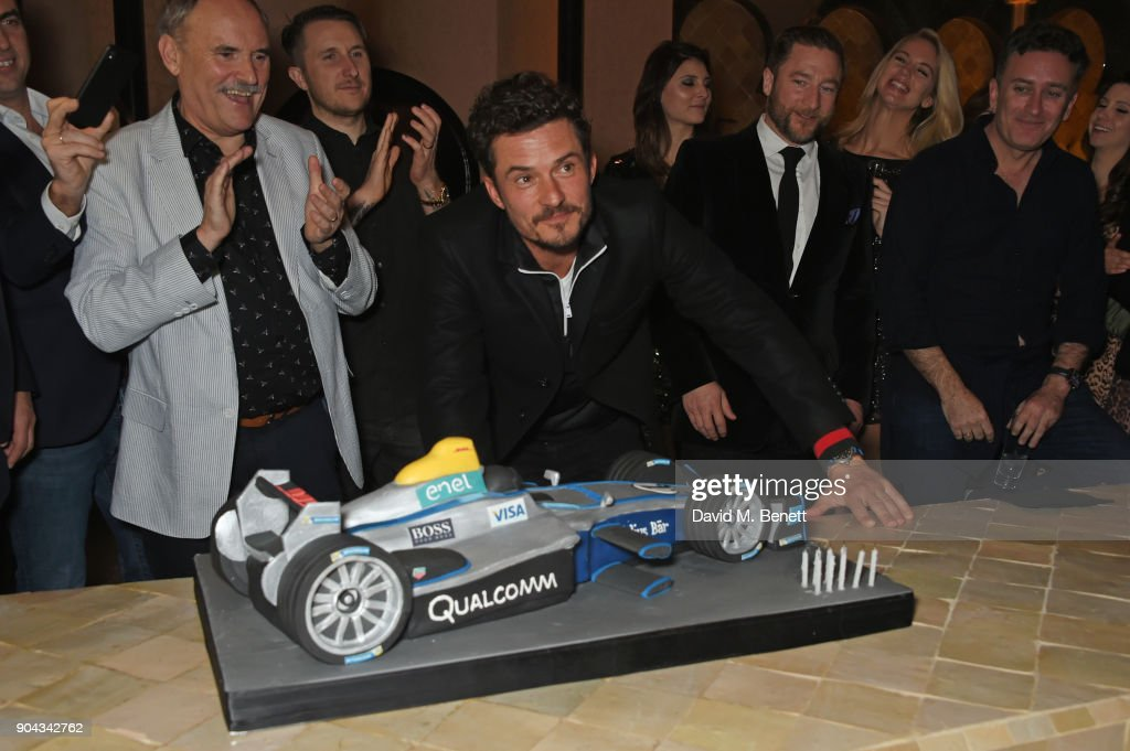 Orlando Bloom (C) poses with his birthday cake as father Colin Stone and friends Scott Campbell, Andres Faucher and FIA Formula E CEO Alejandro Agag look on at Orlando Bloom's birthday party with ABB FIA Formula E Championship at Hotel Amanjena on January 12, 2018 in Marrakech, Morocco.