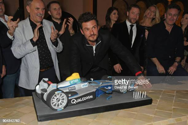 Orlando Bloom poses with his birthday cake as father Colin Stone and friends Scott Campbell Andres Faucher and FIA Formula E CEO Alejandro Agag look...
