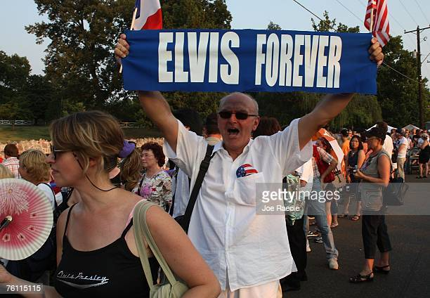 Orlando Bruno from Paris France holds up a banner printed Elvis Forever as he stands in line during a vigil for the late Elvis Presley outside the...