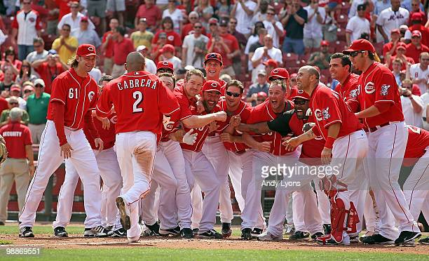 Orlando Cabrera of the Cincinnati Reds is greeted at home plate by teammates after hitting the game winning home run in the 10th inning against the...