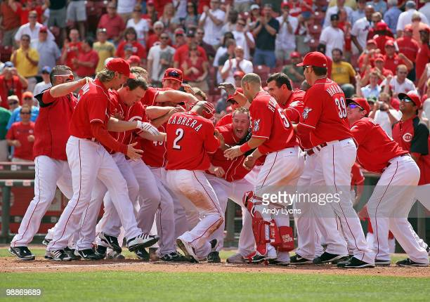 Orlando Cabrera of the Cincinnati Reds is surrounded by teammates after hitting the game winning home run in the 10th inning against the New York...