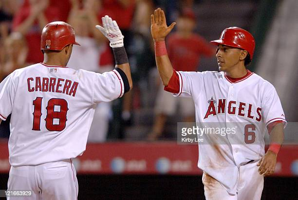 Orlando Cabrera of the Los Angeles Angels of Anaheim is congratulated by Maicer Izturis after a tworun home run in the fourth inning of 105 victory...