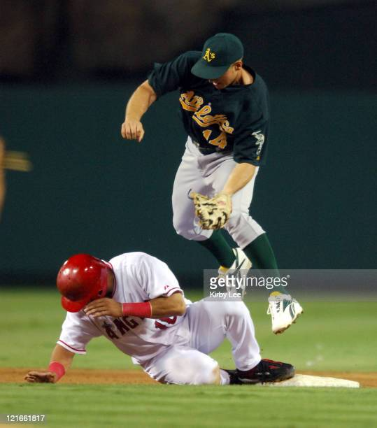Orlando Cabrera of the Los Angeles Angels of Anaheim slides safely into second base beneath tag of Mark Ellis of the Oakland Athletics on a pickoff...