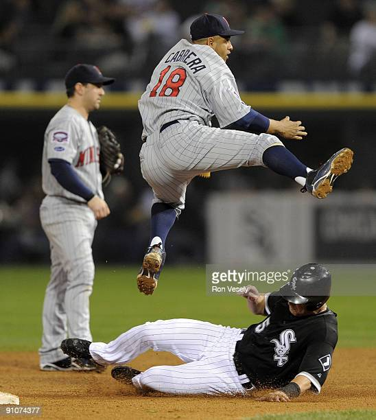 Orlando Cabrera of the Minnesota Twins turns a double play over a sliding Jayson Nix of the Chicago White Sox on September 23 2009 at US Cellular...
