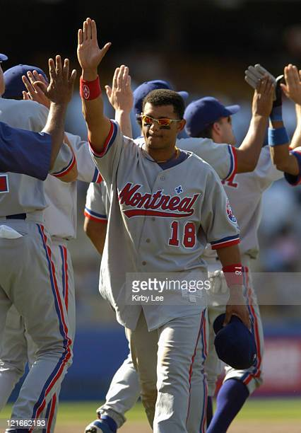 Orlando Cabrera of the Montreal Expos exchanges high fives with teammates after 64 victory over the Los Angeles Dodgers at Dodger Stadium on Sunday...