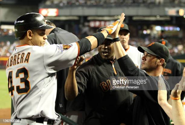 Orlando Cabrera of the San Francisco Giants highfives Ryan Vogelsong after hitting a solo home run against the Arizona Diamondbacks during the fifth...