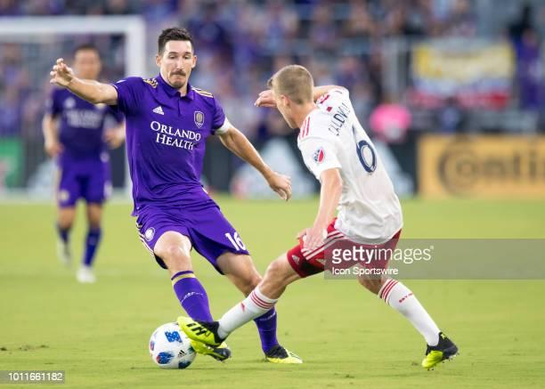 Orlando City midfielder Sacha Kljestan and New England Revolution midfielder Scott Caldwell challenge for possession during the MLS soccer match...