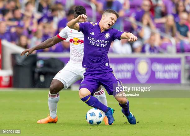 Orlando City midfielder Will Johnson gets fouled from behind by New York Red Bulls forward Carlos Rivas during the MLS soccer match between the...