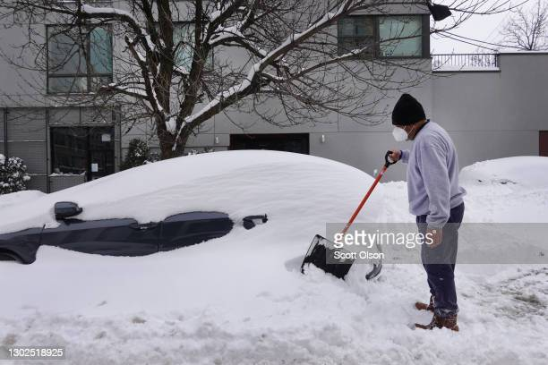 Orlando Flores, who recently moved to Chicago from Texas, digs out his wife's car after it was buried in snow on February 16, 2021 in Chicago,...