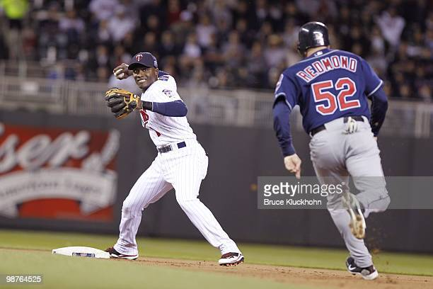 Orlando Hudson of the Minnesota Twins turns a double play against the Cleveland Indians on April 21 2010 at Target Field in Minneapolis Minnesota The...