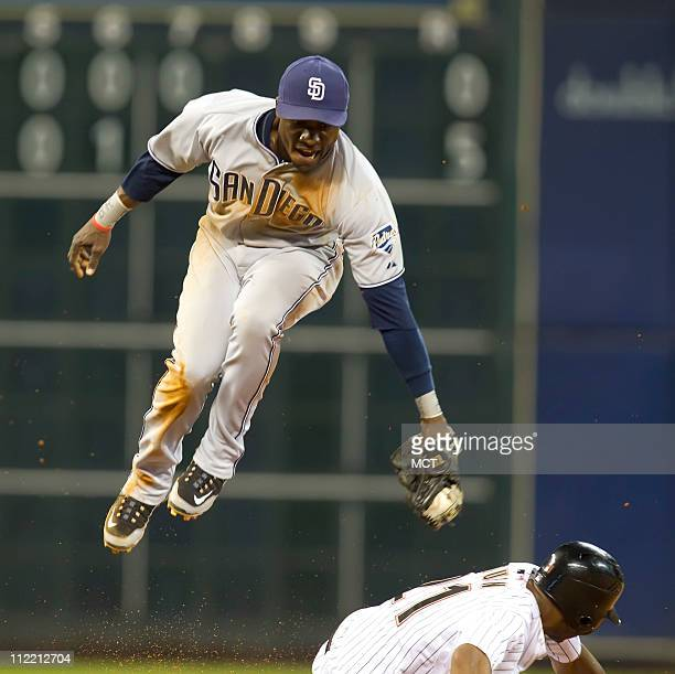 Orlando Hudson of the San Diego Padres can't get the tag down on a high throw as Michael Bourn of the Houston Astros steals second base in the sixth...
