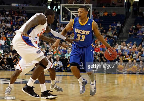 Orlando Johnson of the UC Santa Barbara Gauchos drives against Vernon Macklin of the Florida Gators during the second round of the 2011 NCAA men's...